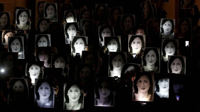 Dalam suatu aksi protes di luar kantor Perdana Menteri Joseph Muscat at Auberge de Castille di Valleta, Malta, penduduk mengacungkan foto wartawan anti-korupsi Daphne Caruana Galizia yang terbunuh 18 bulan lalu. (REUTERS/Darrin Zammit Lupi)