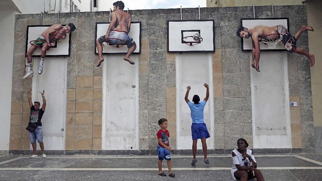 Ada pula gambar pria-pria 'bergelantungan' di ring-ring di lapangan basket. (REUTERS/Fernando Medina)