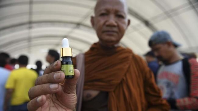 Seorang biksu Buddha menunjukkan botol minyak ganja untuk obat yang telah terdaftar di Festival Ganja Pan Ram, 19 April 2019. (AFP/Lillian SUWANRUMPHA)
