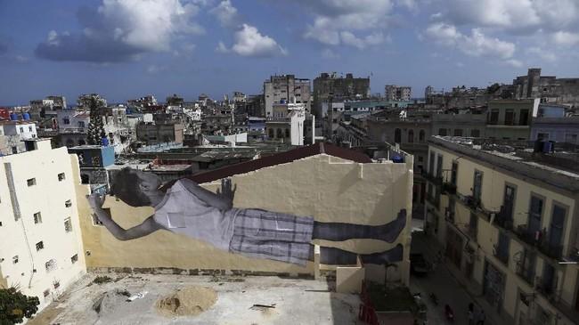 Ada gambar besar berbentuk anak kecil yang mengintip dari dinding yang awalnya polos. (REUTERS/Fernando Medina)