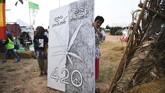 Seorang warga menunjukkan poster daun ganja dengan variasi 420 di festival ganja Pan Ram. 420 atau 16.20 diketahui para pemakai ganja sebagai waktu yang tepat untuk mengonsumsi mariyuana. (AFP/Lillian SUWANRUMPHA)