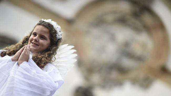 Di Brasil, seorang gadis berdandan bak malaikat yang berjalan di atas permadani serbuk gergaji saat prosesi Paskah yang menggambarkan kebangkitan Kristus di kota bersejarah Ouro Preto, Minggu (21/4). (Photo by Douglas MAGNO / AFP)
