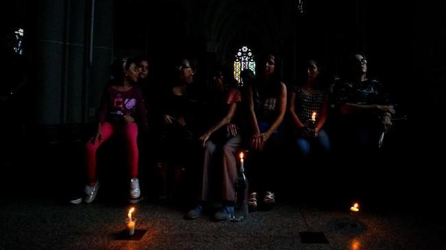Umat Kristiani Venezuela menghadiri Misa sebagai bagian dari perayaan Pekan Suci selama pemadaman di Maracaubo, Sabtu (20/4). (REUTERS/Issac Urrutia)