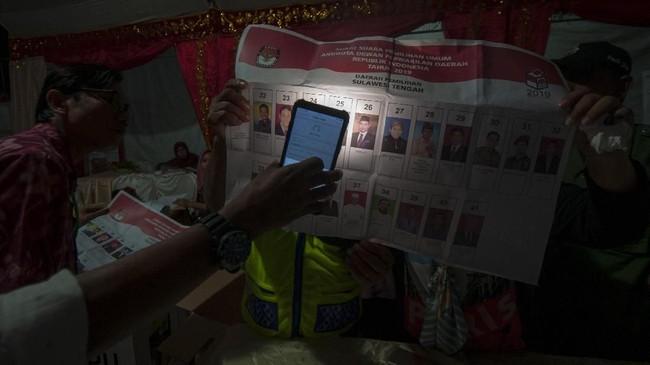 Anggota KPPS memastikan titik pencoblosan surat suara pada penghitungan hasil pemilihan Calon Legislator Dewan Perwakilan Daerah (DPD) di TPS 05 Kelurahan Lolu Utara, Palu, Sulteng, Rabu (17/4). Saat kelelahan mendera, para KPPS pun diharuskan tetap jeli, teliti, dan tegas kala menghitung surat-surat suara. (ANTARA FOTO/Basri Marzuki)