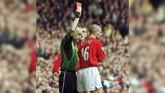 Kapten Man United Roy Keane (kanan) mendapat kartu merah usai melakukan tekel horor ke lutut gelandang Man City Alf-Inge Haland. Akibat tekel tersebut Haland cedera hingga akhir musim dan terpaksa pensiun dini karenatidak bisa pulih sepenuhnya. (ROBIN PARKER / FOTOSPORTS INTERNATIONAL / AFP)
