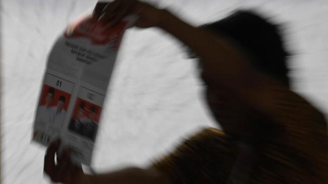 Petugas KPPS menunjukkan surat suara Pilpres ketika melakukan penghitungan surat suara di TPS 05 Sawah Besar. Selain untuk menjamin kelancaran pemungutan dan penghitungan suara, para petugas pun diberi tugas menjamin surat suara yang telah dihitung aman dari kecurangan atau pencurian.(ANTARA FOTO/Wahyu Putro A/wsj.