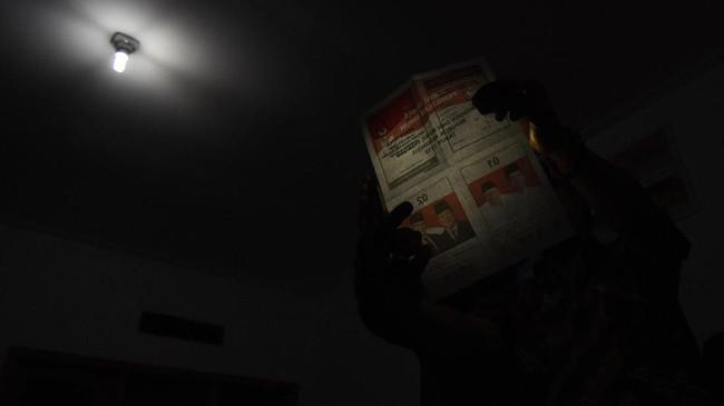 Petugas KPPS melakukan penghitungan suara Pemilu serentak 2019 hingga malam hari di TPS 92, Depok. Beratnya pelaksanaan pemilu 2019 pun membuat Ketua MK Anwar Usman menyampaikan simpati karena putusan peradilan konstitusi turut melanggengkan rencana pelaksanaan pemilu serentak 2019. (ANTARA FOTO/Indrianto Eko Suwarso)