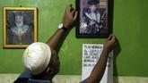 Anggota keluarga memperbaiki posisi foto Sudirdjo, seorang petugas KPPS yang meninggal dunia usai mendapatkan perawatan di rumah sakit di Bekasi, Jawa Barat, Selasa (23/4/2019). KPU Kota Bekasi mencatat sebanyak tiga orang petugas KPPS meninggal dunia usai bertugas di Pemilu serentak 2019. ANTARA FOTO/Risky Andrianto