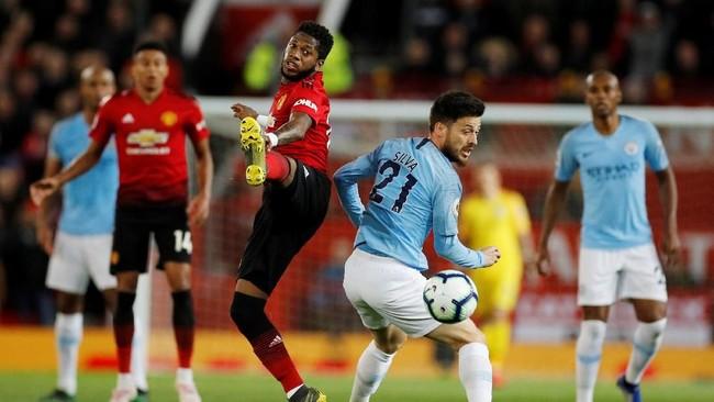 Fred dan David Silva berebut bola di lini tengah. Fred menjadi salah satu pemain Manchester United yang aktif dalam laga melawan Manchester City. (REUTERS/Phil Noble)