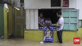 Sejumlah warga Jatinegara memilih bertahan di rumah dan enggan mengungsi. Mereka berharap banjir akan segera surut, Jumat (26/4) malam. (CNN Indonesia/Adhi Wicaksono)