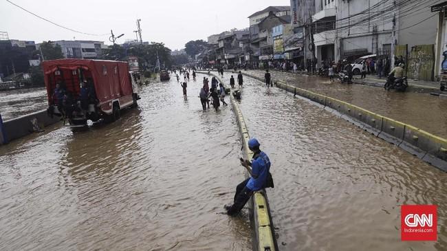 Jalan Jatinegara Barat yang berada persis di pinggir Kali Ciliwung tergenang air luapan kali. Aktivitas warga terganggu,arus lalu lintasyang hendak melintasdialihkan. (CNN Indonesia/Adhi Wicaksono).