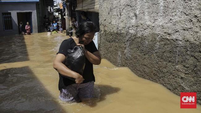 Warga di Balekambang Codet Jakarta Timur , membersihkan sisa-sisa lumpur akibat banjir (26/4). Kiriman debit air dari hulu (Bogor) membuat sejumlah kawasan di bantaran Kali Ciliwung meluap. (CNN Indonesia/Adhi Wicaksono)