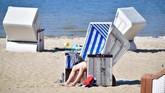Seorang pengunjung duduk di kursi di suatu pantai tempat pemandian terbuka
