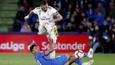 Striker Real Madrid, Karim Benzema, menccoba melewati adangan pemain Getafe. Benzema total hanya melepaskan total tiga tembakan dan cuma satu yang tepat sasaran.(REUTERS/Sergio Perez)