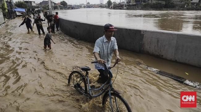 Warga melintasi genangan di kawasan Jatinegara Jakarta Timur, Jumat (26/4). Luapan kali Ciliwung membuat sejumlah jalan tergenang air. Kali meluap setelah hujan mengguyur wilayah Bogor dan menyebabkan debit air naik. (CNN Indonesia/Adhi Wicaksono)