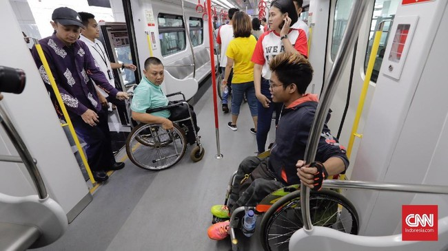 Petugas membantu seorang penyandang disabilitas naik ke kereta LRT di Stasiun LRT Veldrome, Jakarta, Sabtu (27/4). Kegiatan yang diikuti Jakarta Barrier Free Tourism (JBFT) tersebut untuk mengenalkan lebih dekat LRT.