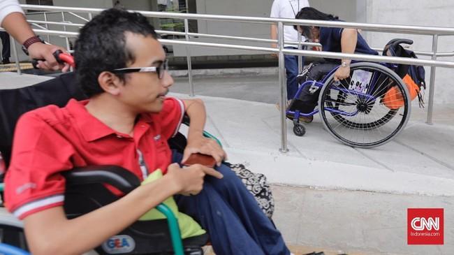 Petugas membantu penyandang disabilitas naik ke kereta LRT di Stasiun LRT Veldrome, Jakarta, Sabtu (27/4). kegiatan yang diikuti Jakarta Barrier Free Tourism (JBFT) tersebut untuk mengenalkan lebih dekat LRT. (CNN Indonesia/Adhi Wicaksono)