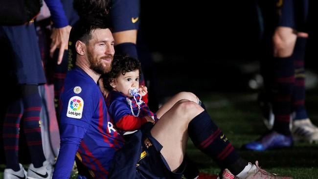 Megabintang Barcelona Lionel Messi juga merayakan pesta juara La Liga bersama anaknya.Ini menjadi gelar La Liga ke-8 yang diraihLa Pulga bersama Barcelona dalam 11 musim terakhir. (REUTERS/Albert Gea)