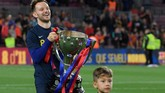 Gelandang Barcelona Ivan Rakitic merayakan pesta juara Barcelona bersama putranya yang ikut larut dalam kegembiraan. (Photo by LLUIS GENE / AFP)
