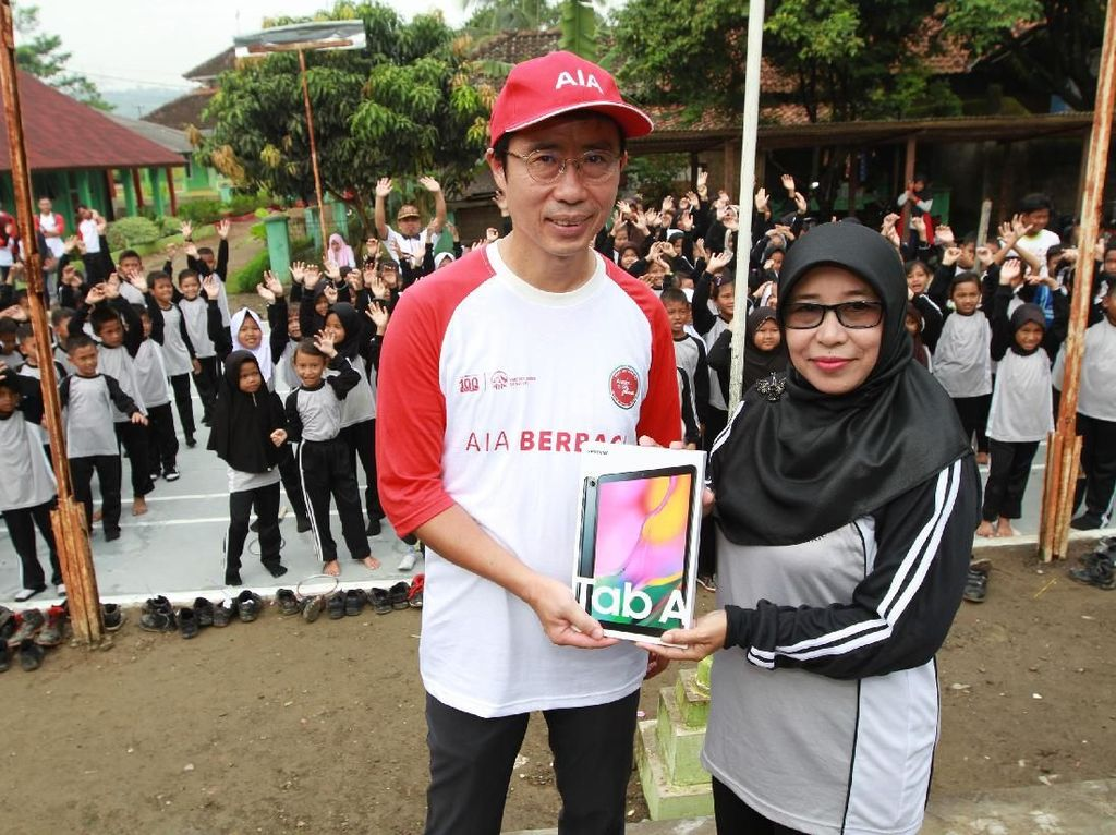 Direktur keuangan PT AIA FINANCIAL Terence Lin (kiri) saat menyerahkan secara simbolis salah satu fasilitas penunjang pendidikan berupa smartphone kepada Kepala Sekolah SD Singasari Jonggol Samsiah di Jonggol, Bogor, Jawabarat, Sabtu (27/04/2019). Istimewa.