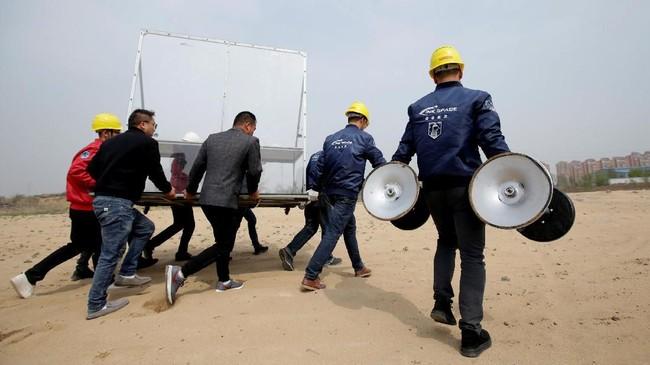 Orang-orang membawa meja yang digunakan sebagai konsol kontrol peluncuran uji coba roket LinkSpace. (REUTERS/Jason Lee)