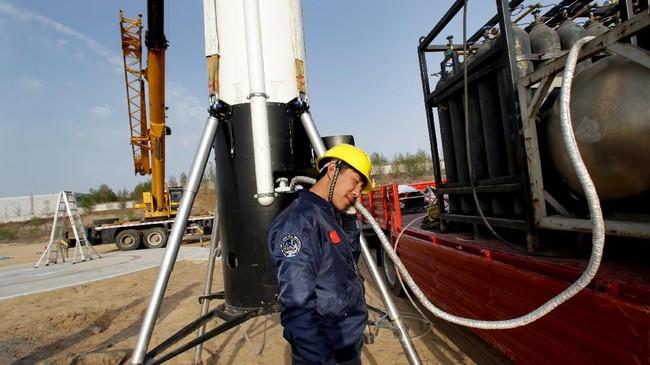 Insinyur Xiu Yu memegangsambil mendengarkan pipa setelah peluncuran uji coba roket LinkSpace yang dapat digunakan kembali di sebidang tanah kosong di Longkou, provinsi Shandong, Cina. (REUTERS/Jason Lee)