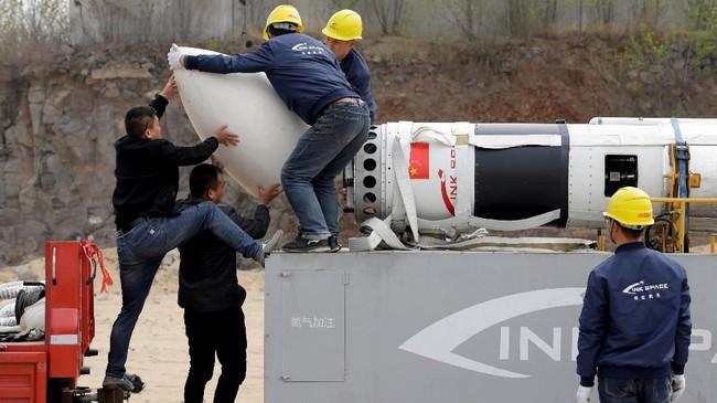 Para ilmuwan sedang memasang payload fairing sebelum peluncuran uji coba roket LinkSpace yang dapat digunakan kembali. (REUTERS/Jason Lee)