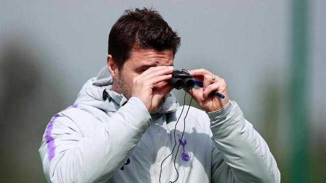 Manajer Tottenham Hotspur Mauricio Pochettino menggunakan teropong saat memimpin latihan terakhir jelang lawan Ajax Amsterdam pada leg pertama semifinal Liga Champions. (Reuters/Andrew Couldridge)
