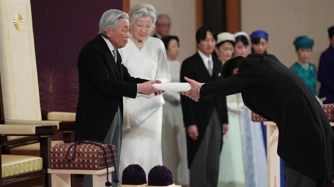 Usai berpidato, Akihito turut menyerahkan simbol kekaisaran yakni pedang, permata, dan cermin serta lencana. (Japan Pool/Pool via REUTERS)