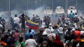 Kelompok demonstran bentrok dengan polisi di jalan-jalan ibukota Venezuela, Selasa (30/4) waktu setempat. Pihak berweang menyiapkan tank untuk menjaga keamanan (REUTERS/Carlos Garcia Rawlins)