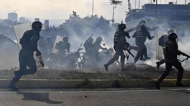 Anggota Pasukan Keamanan Bolivarian yuang setia pada pemerintahan Presiden Nicolas Maduro tengah diantara kepulan asap gas air mata yang ditembakkan pendukung pemimpin oposisi Venezuela yang mendeklarasikan diri sebagai presiden Juan Guaido. (Photo by Yuri CORTEZ / AFP)