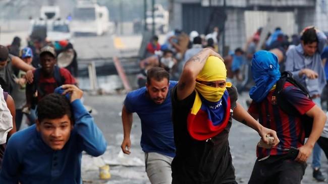 Para demonstran menghadapi tentara militer dan kendaraan mereka di basis lapangan udara Generalisimo Francisco de Miranda Airbase