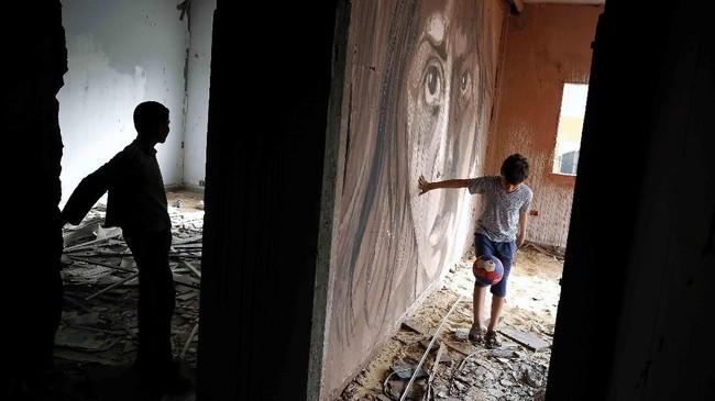 Seorang bocah bermain bola di dekat mural yang dilukis oleh seniman Palestina, Ali Al-Jabali. Mural itu terletak pada suatu bangunan di Gaza yang separuhnya hancur akibat perang antara tentara Israel dan Hamas. (AP Photo/Hatem Moussa)