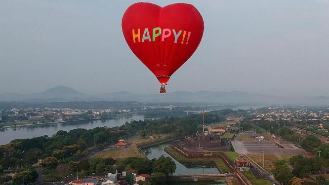 Foto udara ini menunjukkan balon udara yang diterbangkan di atas kota Hue di Vietnam dalam suatu festival balon udara. (Photo by Manan VATSYAYANA / AFP)