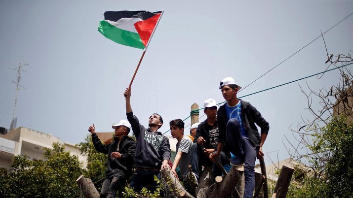 Palestinians climb over a tree during a rally marking International Workers' Day, or Labour Day, in Gaza City May 1, 2019. REUTERS/Mohammed Salem
