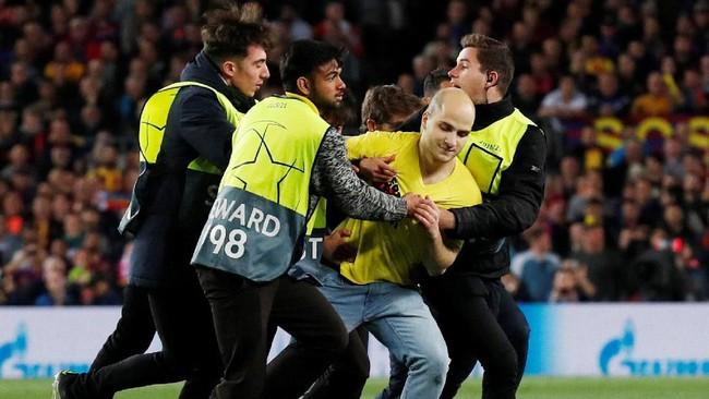 Seorang penyusup yang masuk ke lapangan ditangkap oleh petugas pertandingan. (REUTERS/Albert Gea)