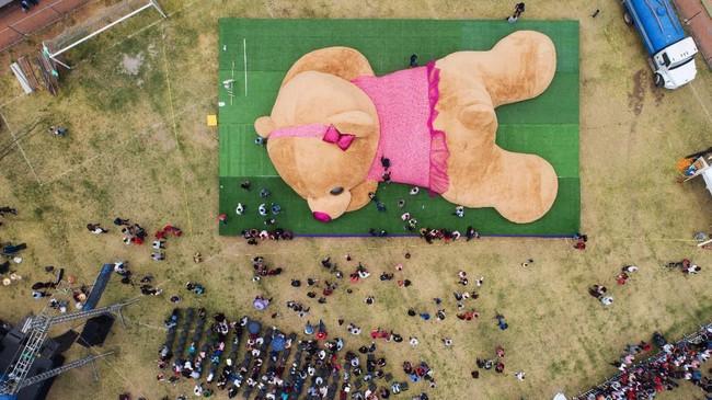 Dalam foto udara di Xonacation Meksiko ini, para petugas sedang mengukur boneka beruang raksasa yang diperkirakan memiliki panjang lebih dari 20 meter dan berat lebih dari 4 ton. Boneka ini memecahkan rekor dunia sebagai boneka beruang raksasa terbesar. (Photo by MARIO VAZQUEZ / AFP)
