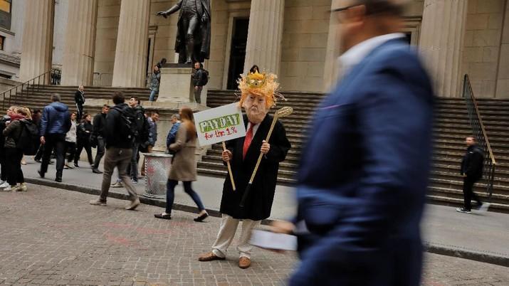 Seorang pemrotes yang mengenakan topeng memegang tanda di depan Federal Hall pada rapat umum May Day di Wall Street di Manhattan di New York City, New York, AS, 1 Mei 2019. REUTERS / Lucas Jackson