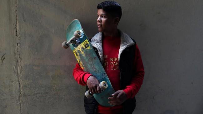 Seorang anggota Gaza Skate Team, Mustafa Sarhan (19), berpose bersama papan skateboard 'butut' kesayangannya.