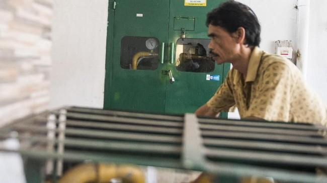 Pekerja melintas di depan gardu gas PGN di pusat pengolahan makanan ringan Klitik Irwan di Cirebon, Jawa Barat. (M Agung Rajasa)