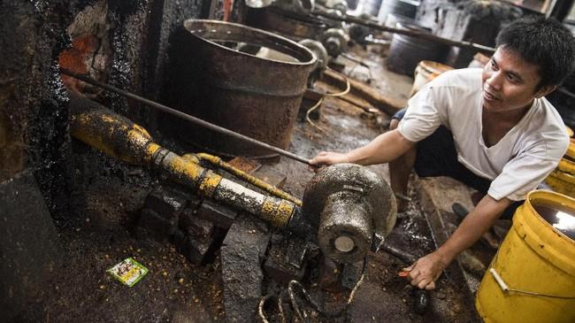 Pekerja memeriksa mesin blower gas sebelum memasak jagung di pusat pengolahan makanan ringan. (M Agung Rajasa).