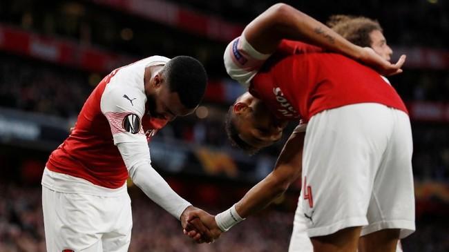 Alexandre Lacazette dan Pierre-Emerick Aubameyang bersalaman merayakan gol Arsenal. Skor 2-1 untuk Arsenal bertahan hingga akhir babak pertama. (Reuters/Paul Childs)