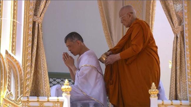 Proses penobatan raja diawali saat raja Rama X yang mengenakan seragam militer putih berganti mengenakan jubah putih. Setelah mengenakan jubah, wajah dan sejumlah bagian tubuh Raja Thailand kesepuluh ini dibasuh menggunakan air suci yang diambil dari seluruh penjuru Thailand. (REUTERS/Reuters TV)