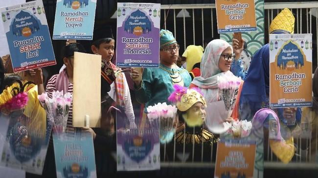 Sejumlah pelajar SD Muhammadiyah 4 Surabaya melakukan aksi memperingati datangnya bulan suci di Surabaya, Jawa Timur, Selasa (30/4/2019). Aksi bentang poster, bagi bunga dan selebaran jadwal imsak itu untuk menyambut bulan Ramadan. ANTARA FOTO/Didik Suhartono