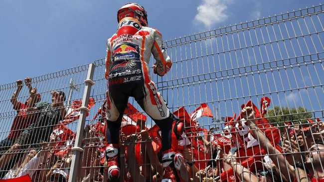 Marc Marquez menaiki pagar usai menang di MotoGP Spanyol 2019. Dengan torehan 70 poin, Marquez unggul satu poin atas Alex Rins di klasemen MotoGP 2019. (AP Photo/Miguel Morenatti)
