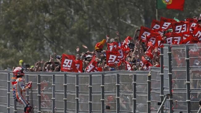 Marc Marquez berusaha menaiki pagar untuk merayakan kemenangan bersama pendukung. Marquez kembali ke puncak klasemen MotoGP 2019 usai kemenangan di Jerez. (REUTERS/Jon Nazca)