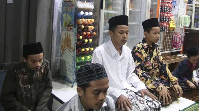 Sejumlah santri melakukan shalat tarawih pertama di dalam warung kawasan pondok pesantren (ponpes) Lirboyo, Kota Kediri, Jawa Timur, Minggu (5/5) malam. Lirboyo dikenal sebagai salah satu ponpes besar di Jawa Timur. (ANTARA FOTO/Prasetia Fauzani)