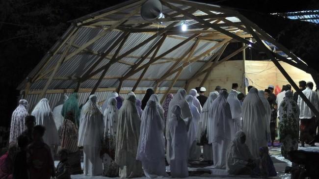 Sejumlah umat muslim pengungsi korban bencana gempa dan tsunami melaksanakan salat tarawih pertama dengan menggunakan tempat ibadah sementara di Palu, Sulawesi Tengah, Minggu (5/5). (ANTARA FOTO/Mohamad Hamzah)