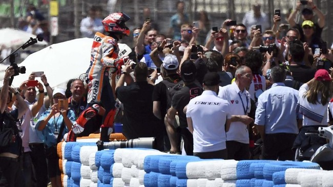 Pebalap Repsol Honda Marc Marquez merayakan kemenangan di MotoGP Spanyol 2019 bersama pendukung di Sirkuit Jerez-Angel Nieto. (GABRIEL BOUYS / AFP)