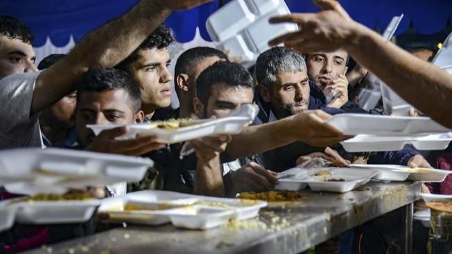 Di bagian tenggara Turki, Diyarbakir, umat Muslim mengantre sajian berbuka puasa di hari pertama Ramadan, Senin (6/5). (Photo by Ilyas AKENGIN / AFP)